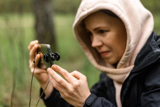 Телефонные линзы для макросъемки женщина держит мобильный телефон
