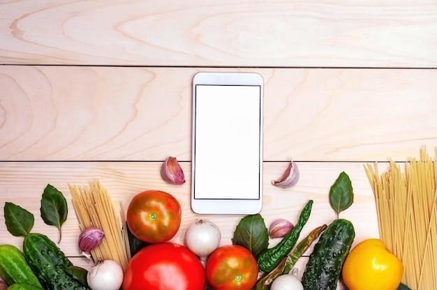 Макет телефона на фоне деревянной доски и овощей.