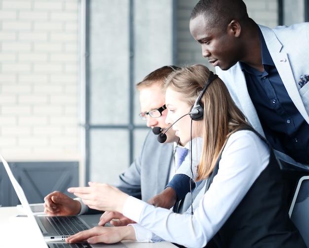 Оператор по телефону, работающий в офисе call-центра, помогает своему коллеге