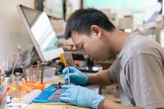 전화 수리 개념은 스크루드라이버를 사용하여 전자 장치의 부품을 고정하는 젊은 전기 기술자입니다.