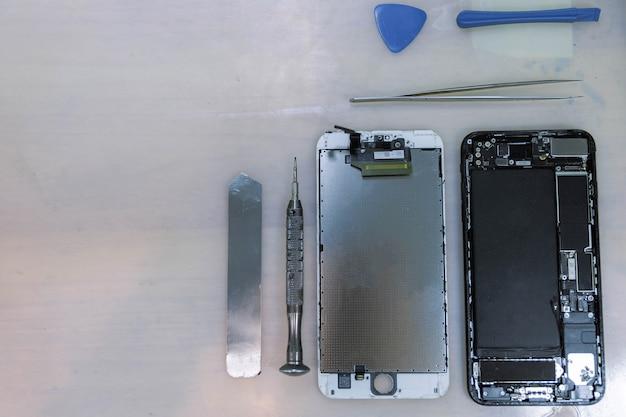 전화 수리 개념 스마트 폰의 구성 요소는 핀셋, 쇠 막대, 작은 드라이버를 포함한 스테인리스 도구 근처의 부품으로 분리됩니다.