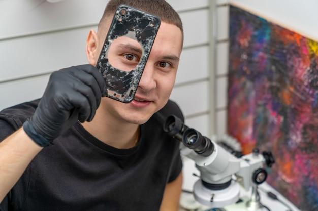 電話修理工は片目でスマートフォンの蓋の穴をのぞきます