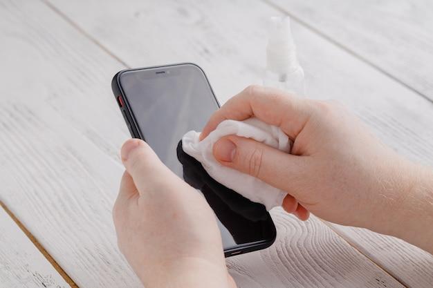 Дезинфекция экрана телефона, протирка, удаление микробов антибактериальными салфетками от вируса короны covid-19