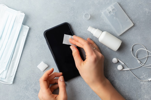 Экран телефона дезинфицирует, протирает женщину, убирает микробы антибактериальными салфетками от вируса короны covid-19