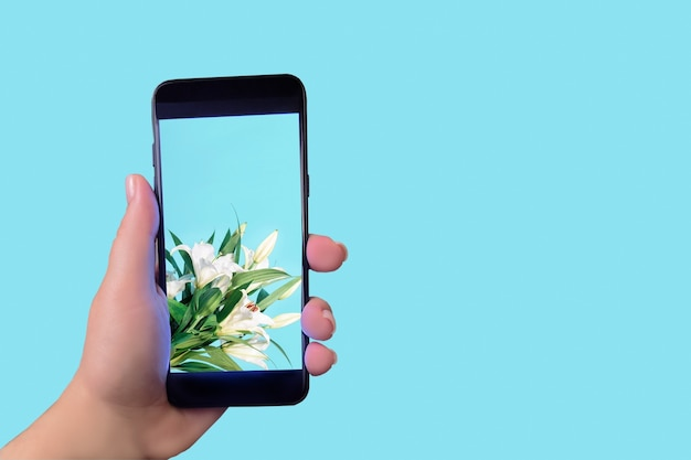 Phone on screen flowers in hand