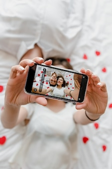 Phone screen with selfie of man and woman in love in bed kissing