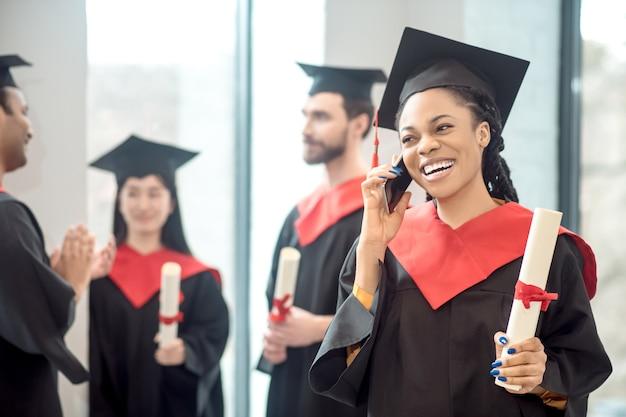 On the phone. smiling dark-skinned graduate talking on the phone