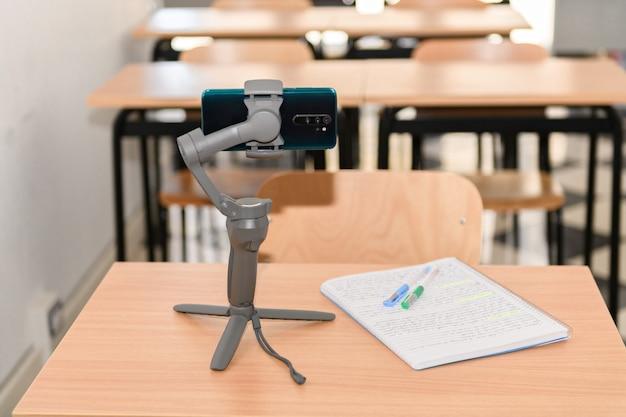 Стабилизатор телефона с телефоном на столе с канцелярскими принадлежностями в пустом классе