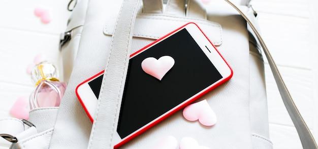 電話、スタイリッシュなバッグ、白い背景の上の香水。心のこもった美しいフラットレイ。女の子への最高のプレゼント。女性または母の日のアイデア。
