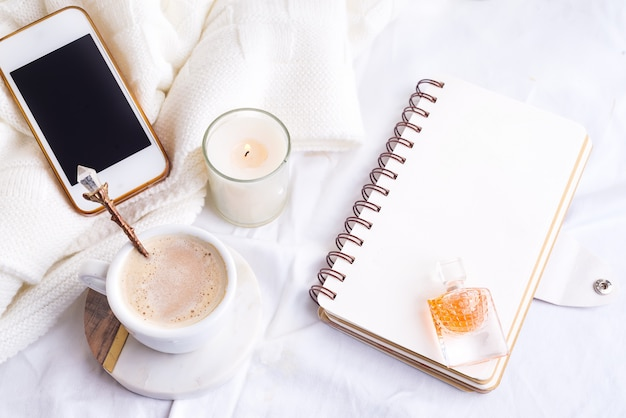 Phone, white cup of coffee and candle with notebook on white bed and plaid, cozy morning light.