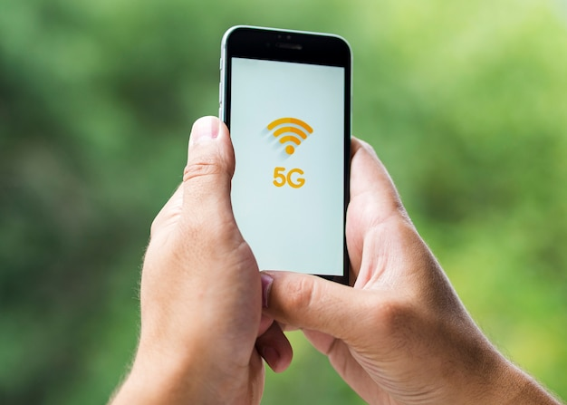 Phone with 5g on screen held in hands