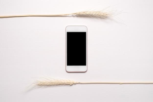 白いテーブルの上に乾燥した白い花と黒い画面と電話