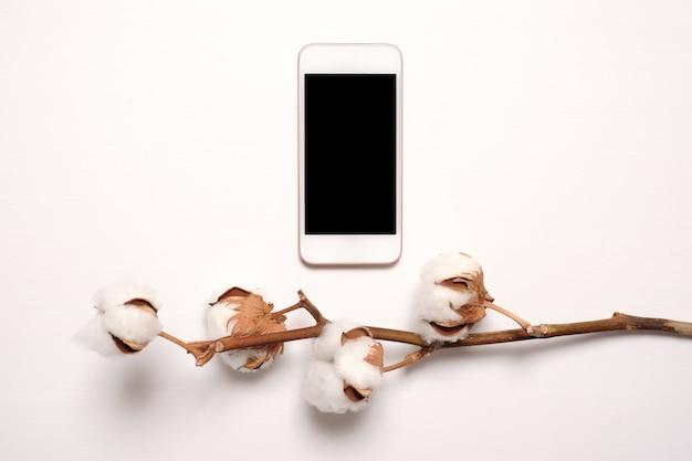 乾燥した綿の花が付いている黒い画面が付いている電話