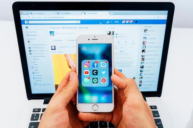Facebookとアプリとノートパソコンを搭載した携帯電話 Premium写真