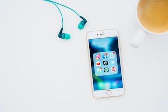 Phone with apps, coffee mug and earphones