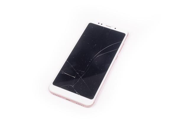 Телефон с разбитым сенсорным стеклом, изолированным на белой стене