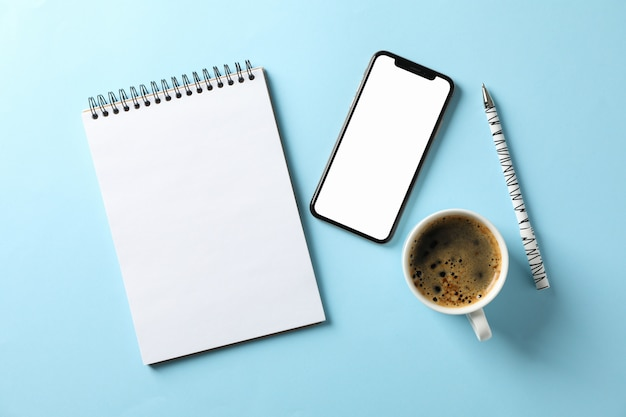 Phone with empty screen, copybook, pen and cup of coffee on blue background, top view