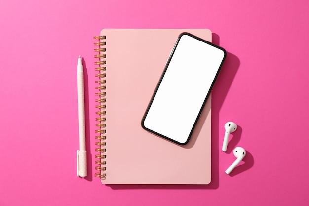 Телефон с пустым экраном, наушниками, тетрадью и ручкой на розовой поверхности