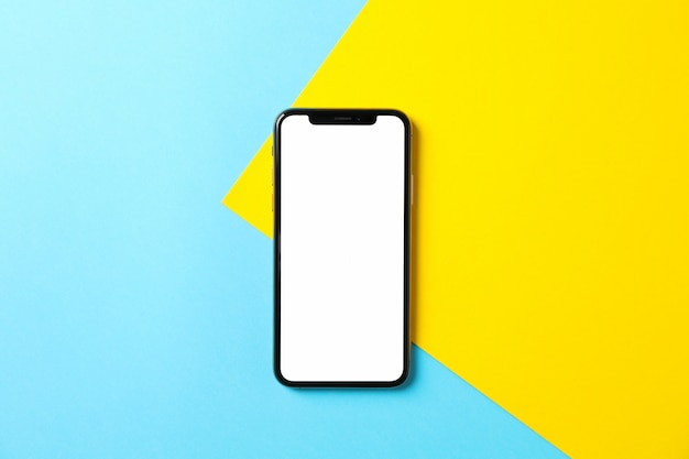 Phone with empty screen on two tone background, top view