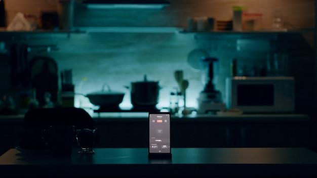 ハイテクアプリケーションで光を制御する、誰もいないキッチンのテーブルに置かれたインテリジェントソフトウェアを備えた電話。空家自動化システムのスマートホームアプリを備えたモバイル