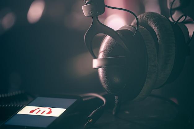 ぼやけた背景、音楽リスニングコンセプト、コピースペースに音楽アイコンとヘッドフォンを備えた電話。