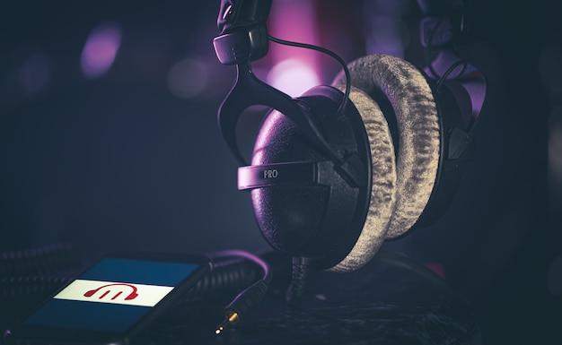 Телефон с музыкальным значком и наушниками на размытом фоне, концепция прослушивания музыки, копией пространства.