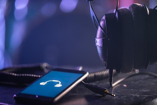 Telefono con icona della musica e cuffie su sfondo sfocato, concetto di ascolto di musica, spazio di copia.