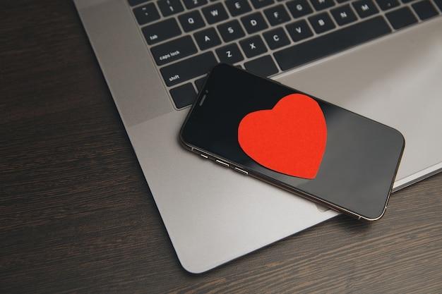 Телефон с красными сердечками на столе