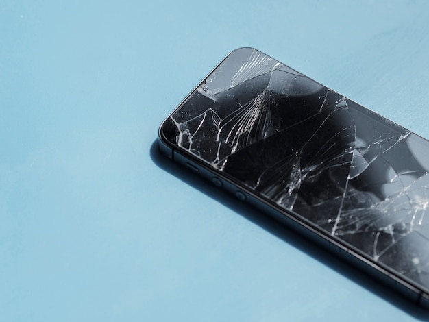 Phone with shattered screen on blue background