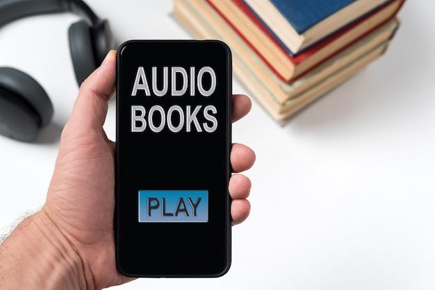 책과 헤드폰의 배경에 손에 오디오북이 새겨진 전화. 오디오북을 듣고 있습니다.