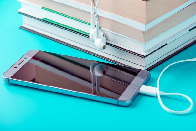 本のスタックの横にある白いイヤホン付きの電話