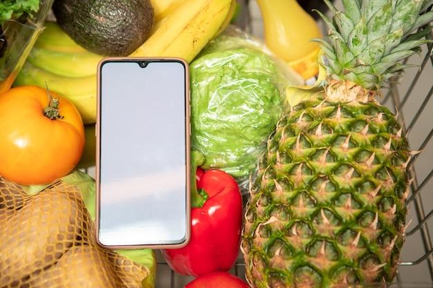 果物や野菜の健康食品と食料品のショッピングカートの白い画面のコピースペースを持つ電話