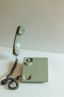 灰色の背景にボタンのない電話。抽象化。シュルレアリスム。