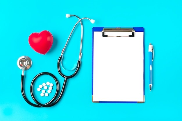 Phonendoscope, heart, tablet with white paper, pen, medicine on blue background