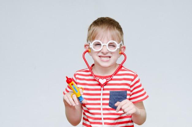 いたずら好きな少年が医者を演じます。おもちゃの注射器、メガネ、phonendoscope。肖像画
