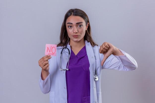 孤立した白い背景の上に親指で嫌悪を示すメッセージが表示されていないリマインダー紙を保持しているphonendoscopeと白衣の若い女性医師