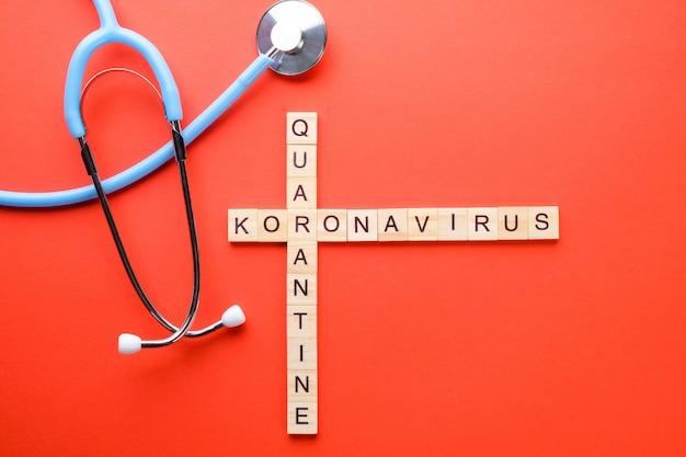 医療テーマのクロスワードと赤の背景にphonendoscope。パンデミック検疫のコンセプト