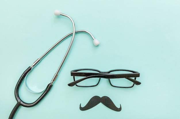 男のヘルスケアの概念。トレンディなパステルブルーの背景に分離された口ひげの医学機器聴診器またはphonendoscopeメガネサイン