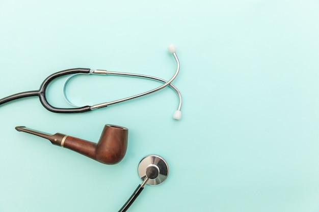 男のヘルスケアの概念。トレンディなパステルブルーの背景に分離された医学機器聴診器またはphonendoscope喫煙パイプ
