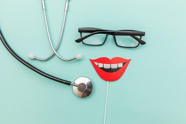健康歯科治療のコンセプト。医療機器の聴診器またはphonendoscopeメガネ笑顔歯のサイン