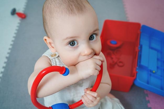 子供はおもちゃをかじります。赤ちゃんは一連の医者と遊ぶ。小さな子供は、phonendoscopeで遊んでいます。
