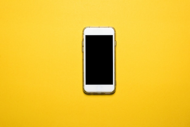Phones, communication devices placed on a yellow background technology concept with copy space