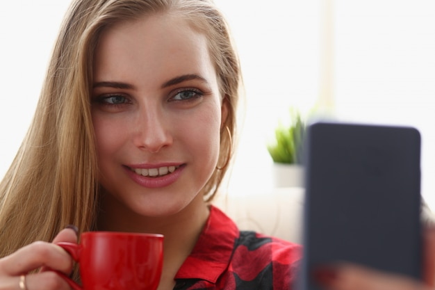 Phonwoman drinking coffe and look at smartphone