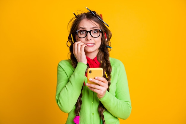 Phoro of frightened girl messy hairdo bite nails hold smartphone wear shirt isolated yellow color background
