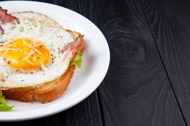 暗い背景の木の白い皿に卵とベーコンのグリルトーストのビューを閉じます。コピースペース。朝食の食べ物phoro。上面図