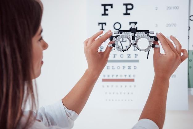 フォロプターは女の子の正面にあります。後ろからの写真。眼鏡の目のチャートを通して見ている女性。