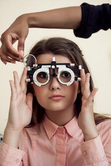 Горизонтальная съемка заинтересованной и любознательной кавказской девушки на встрече с phoropter специалиста ухода за глазами нося пока офтальмолог проверяя ее зрение, сидя над желтой стеной