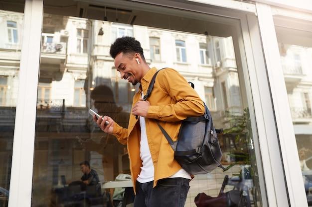 Портрет молодого веселого темнокожего парня в желтой рубашке, идущего по улице, держит телефон, болтает с друзьями, широко улыбается, выглядит счастливым.