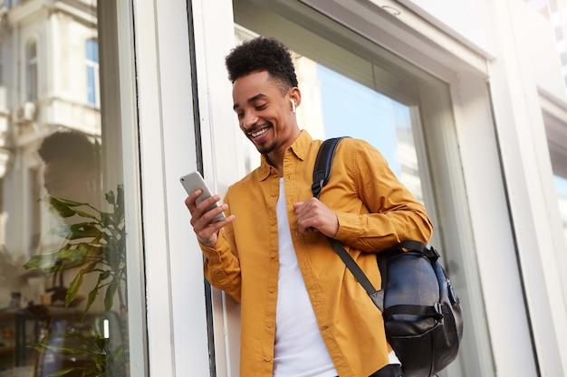 Phortrait di giovane ragazzo afroamericano allegro in camicia gialla, cammina per strada e tiene il telefono, chiacchiera con gli amici, sembra felice e ampiamente sorridente.