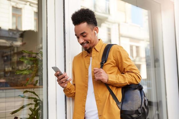 Phortrait di giovane ragazzo afroamericano allegro in camicia gialla, cammina per strada e tiene il telefono, ha ricevuto un messaggio con un simpatico gattino, sembra felice e ampiamente sorridente.